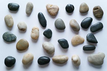 白い紙の背景に置いた複数の小石。平置きの俯瞰撮影。