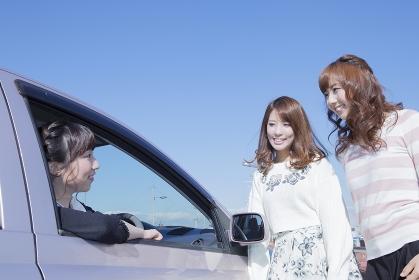 車を停めて友達と会話をする女性