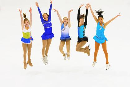 ジャンプするフィギュアスケートの女性達