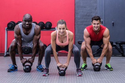 Three muscular athletes about to lift a kettle bell