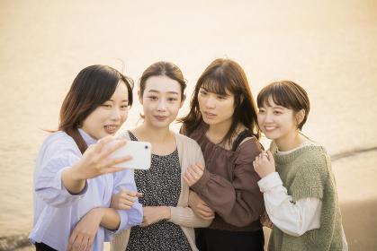 スマートフォンで記念撮影をする女性4人