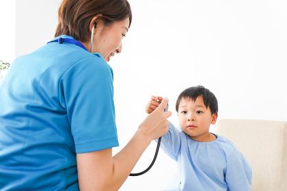 子どもを診察する若い看護師