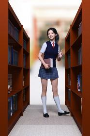 図書室の木の本棚の間でベストを着た女子生徒が本を手に持ち返却しようと場所を確認している