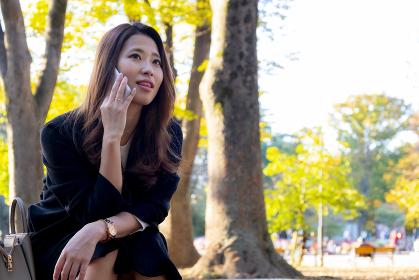 【東京都】屋外で電話を掛ける女性【2020年 紅葉】