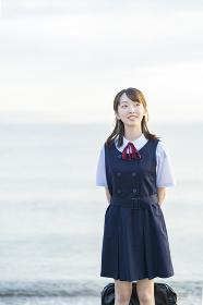 海を背景に、笑顔を見せる女子高生