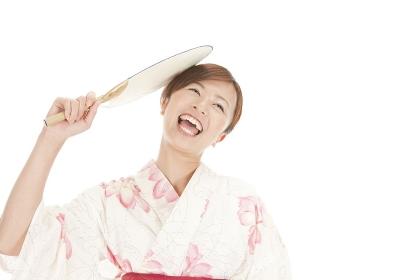 団扇で自分の頭をたたく浴衣女性