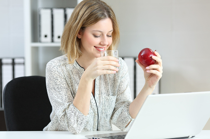 Office worker drinking water and eating an apple