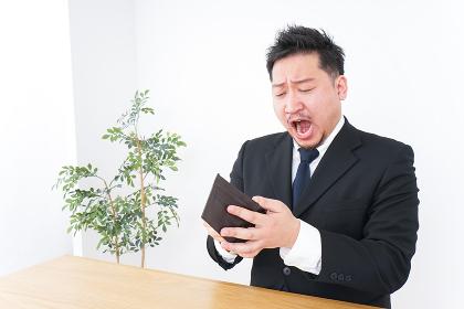 財布を見て驚くビジネスマン
