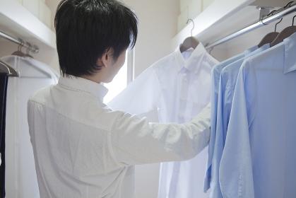 クローゼットでシャツを選ぶ男性
