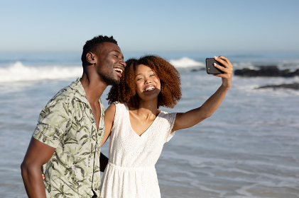 A mixed race couple enjoying free time on beach on a sunny day together, taking photos with a smartphone and holding each other with sun shining on their faces.