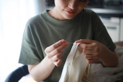 服にボタンを付ける女性