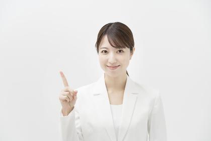 指を上げるポーズをする、白いスーツを着た女性