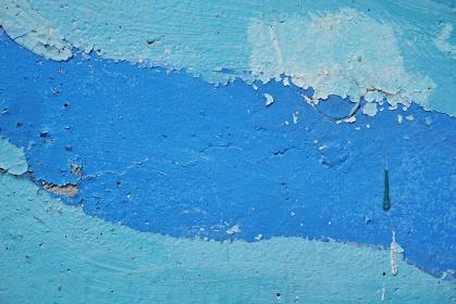青色と水色のペンキが塗られた古いコンクリートの壁