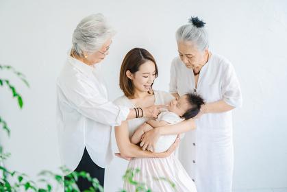 赤ちゃんを抱っこするお母さんと2人のシニア女性