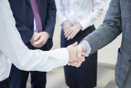 会議室で握手をするビジネスマンの手元