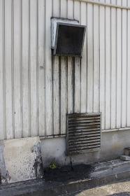 飲食店の外壁のかなり汚れた換気扇と換気口
