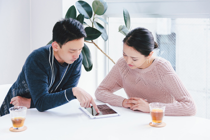 タブレットPCを見て会話するカップル