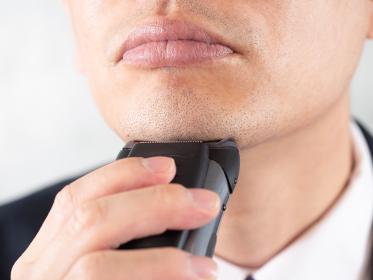 電気シェーバーでアゴの髭を剃る男性ビジネスマン