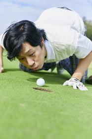 ゴルフボールを吹く日本人男性