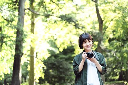新緑の中、カメラを持つ女の子