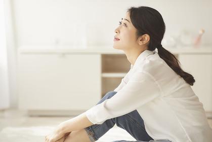 部屋で体育座りをする日本人女性