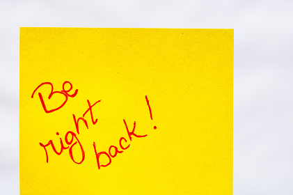 Be right back handwriting text close up isolated on orange paper with copy space. Writing text on memo post reminder