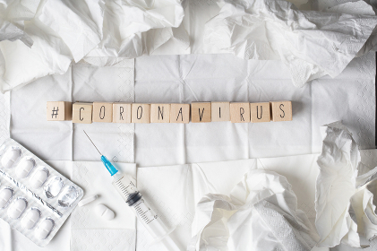 Coronavirus disease named 2019-nCoV on wooden cubes with hashtag on white tissue and medical supplies