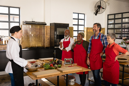 Side view of a multi-ethnic group of Senior adults at a cookery class, the diverse adult students listening to instructions from a Caucasian female chef wearing chefs whites and a black hat and apron, standing around a wooden table of ingredients wearing red aprons, smiling