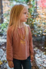 Little girl standing in forest with fall scenery