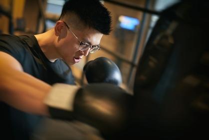 トレーニングジムでキックボクシングをするアジア人男性