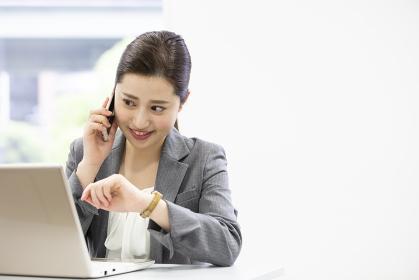 通話しながらPCを操作する日本人女性
