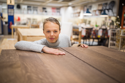 Pretty, young woman choosing the right furniture for her apartment in a modern home furnishings store (color toned image  shallow DOF)