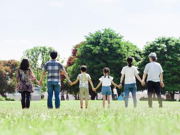 晴れた公園で手をつなぐ三世代家族