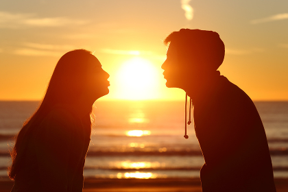 Couple kissing sun with love at sunset