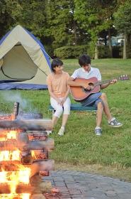 キャンプ中のカップルとキャンプファイヤー