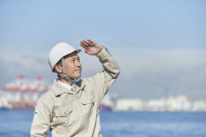 ヘルメットを着用する作業着の日本人男性