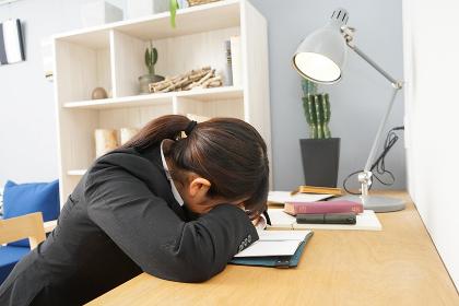 スーツを着て机で寝る女性