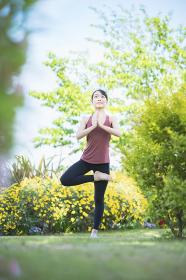 緑あふれる公園でヨガをする若い女性
