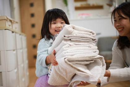 たたんだ洗濯物を運ぶ女の子