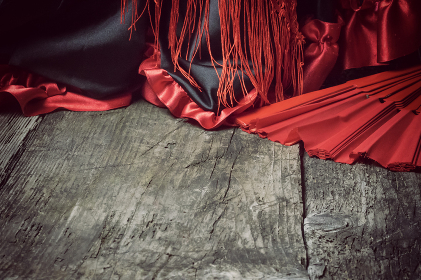 Clothing for Flamenco dance and red fan on the wooden desk.