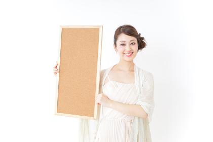 コルクボードを持つドレス姿の女性