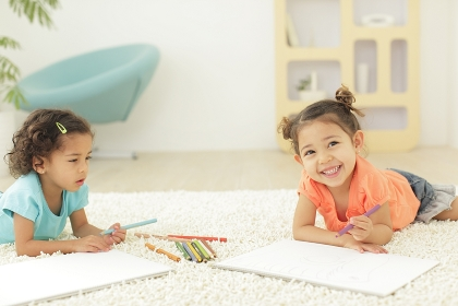 白い画用紙にお絵かきをする女の子たち