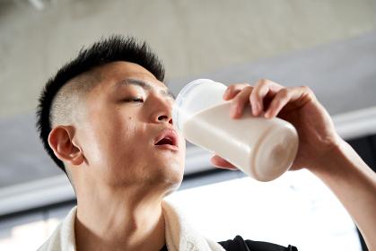 トレーニング後にプロテインを飲むアジア人男性