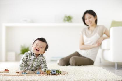 リビングで遊ぶ赤ちゃんと見守るお母さん