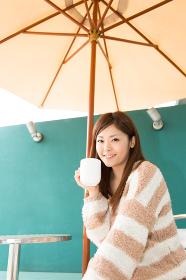 オープンカフェで飲み物を飲む女性