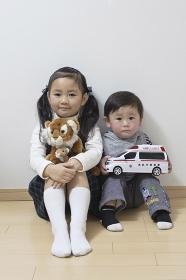 姉弟で仲良くおもちゃを持ってお座り