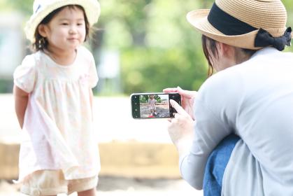 砂場で遊ぶ子供をスマートフォンで撮影する母親