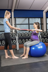 Trainer and pregnant woman using a resistance band
