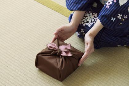 贈り物を差し出す和服姿の女性の手元