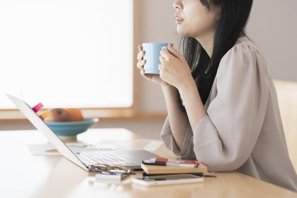 在宅での仕事中に休憩する女性